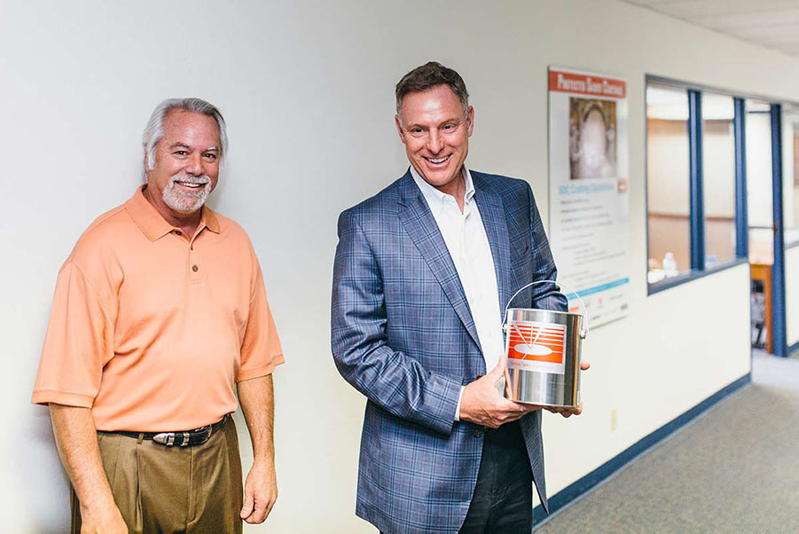 Rep. Peters (right) holds a can of Surface Optics Corporation's spectrally tailored paint, next to Bill Mohar, Director of Commercial Instrument Sales (left).