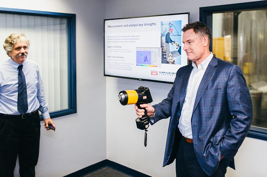 Rep. Peters (left) holding the SOC410-Solar reflectometer, a device for evaluating solar receivers, telescope mirrors, and green building materials.
