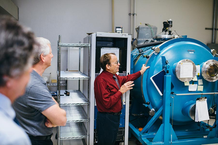 Jonathan Dummer, CEO, with arm resting on 1.5 meter vacuum chamber in coatings lab
